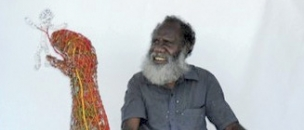 Pormpuraaw Artist Sid Bruce sits next to his Ghost Net sculpture